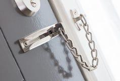 Deurketen op een grijze deur stock afbeeldingen