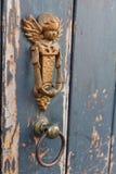 Deurkloppers in de vorm van Engel op een rustieke houten deur Stock Afbeeldingen