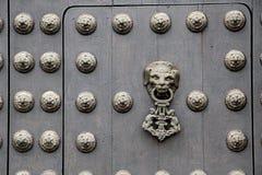 Deurkloppers op zware houten deur op een kerk in de Andes stock foto