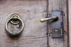 Deurknop en kloppers op oude houten deur Stock Afbeeldingen