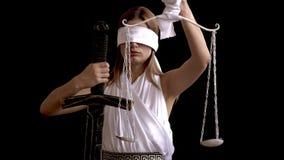 Deusa grega da mulher de justiça Femida com espada à disposição e de escalas no fundo preto ideia do conceito de uma empresa de a video estoque