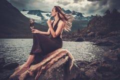 Deusa nórdica no vestuário ritual com o falcão perto do lago selvagem da montanha no vale de Innerdalen foto de stock