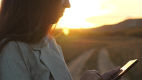 Deushka`s fingers guide their fingers across tablet. businesswoman checks email. Business woman working on tablet at. Sunset in park. Agronomist working with stock video