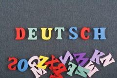 Deutsch, deutsches Wort auf dem schwarzen Bretthintergrund verfasst von den hölzernen Buchstaben des bunten ABC-Alphabetblockes,  Lizenzfreie Stockfotos