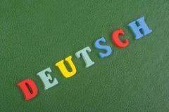 DEUTSCH-Wort auf dem grünen Hintergrund verfasst von den hölzernen Buchstaben des bunten ABC-Alphabetblockes, Kopienraum für Anze Lizenzfreie Stockbilder