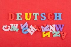 DEUTSCH-Wort auf dem roten Hintergrund verfasst von den hölzernen Buchstaben des bunten ABC-Alphabetblockes, Kopienraum für Anzei Stockfotografie