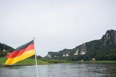 Deutsche Flagge an der Fähre durch die Elbe an Dorf Kurort Rathen und an Bastei-Felsen Stockbilder