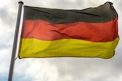 Deutsche Flagge gegen bewölkten Himmel als Metapher für stürmische Zeiten lizenzfreie stockbilder