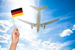 Deutsche Flagge gegen Flugzeugfliegen durch Himmel Lizenzfreies Stockfoto