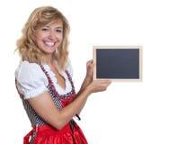 Deutsche Frau im traditionellen bayerischen Dirndl, der Kreidebrett darstellt Lizenzfreie Stockbilder