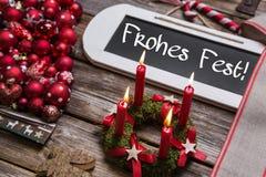 Deutsche Karte der frohen Weihnachten mit vier roten brennenden Kerzen Stockbild