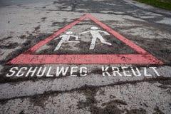 Deutsche Kinder, die Zeichen-Bürgersteigs-Verkehrszeichen Asphalt Deta kreuzen Stockfoto