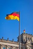 Deutsche Staatsflagge, die vor deutschem Parlament buildi wellenartig bewegt Stockbilder