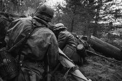 Deutsche Wehrmacht-Infanterie-Soldaten in Zweiter Weltkrieg verstecktem Sittin lizenzfreie stockfotografie