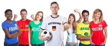 Deutscher Fußballfan mit Ball und zujubelnde Gruppe anderer Fans Lizenzfreies Stockfoto