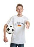 Deutscher Fußballfan mit dem blonden Haar und Ball, der sich Daumen zeigt Lizenzfreies Stockfoto