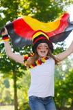 Deutscher Fußballfan, der ihre Flagge wellenartig bewegt Stockfotografie