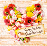 Deutscher Geburtstag wünscht auf einem bunten Blumenherzen Stockfotografie