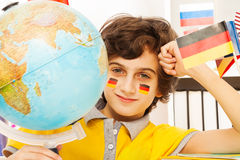 Deutscher Schüler, der Geografie mit einer Kugel studiert Lizenzfreies Stockfoto