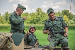 Deutscher Soldat, der mit Kameraden auf einem Behälter spricht Stockbilder