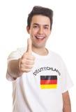 Deutscher Sportfan mit dem schwarzen Haar, das sich Daumen zeigt Lizenzfreies Stockfoto