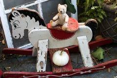 Deutscher Teddybär der Weinlese betreffen ein antikes hölzernes Schaukelpferd lizenzfreie stockfotografie
