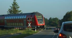 Deutscher Zug und ein Auto am Bahnübergang Lizenzfreies Stockfoto