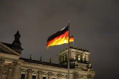 Deutsches fahnenschwenkendes im Wind an Reichstag-Gebäude nachts lizenzfreies stockbild