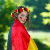 Deutsches Fußbalgebläse umgeben von der deutschen Markierungsfahne Lizenzfreies Stockbild
