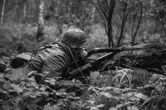 Deutsches verstecktes Sitzen Wehrmacht-Infanterie-Soldat-In World Wars II stockfoto
