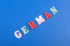 Deutsches Wort auf dem blauen Hintergrund verfasst von den hölzernen Buchstaben des bunten ABC-Alphabetblockes, Kopienraum für An Stockfotografie