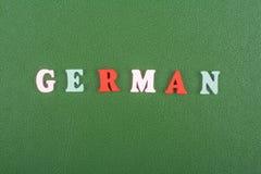 Deutsches Wort auf dem grünen Hintergrund verfasst von den hölzernen Buchstaben des bunten ABC-Alphabetblockes, Kopienraum für An Stockfoto