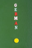 Deutsches Wort auf dem grünen Hintergrund verfasst von den hölzernen Buchstaben des bunten ABC-Alphabetblockes, Kopienraum für An Stockbilder