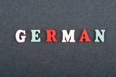 Deutsches Wort auf dem schwarzen Bretthintergrund verfasst von den hölzernen Buchstaben des bunten ABC-Alphabetblockes, Kopienrau Stockfoto