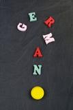 Deutsches Wort auf dem schwarzen Bretthintergrund verfasst von den hölzernen Buchstaben des bunten ABC-Alphabetblockes, Kopienrau Stockbilder