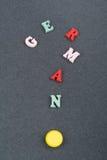 Deutsches Wort auf dem schwarzen Bretthintergrund verfasst von den hölzernen Buchstaben des bunten ABC-Alphabetblockes, Kopienrau Stockbild