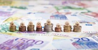 Deutsches Wort Reichtumg auf Münzenstapeln, Bargeldhintergrund Stockfotografie