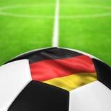 Deutschland flaggamodell av en fotbollboll i grönt gräs Arkivfoton