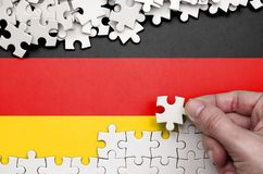 Deutschland-Flagge wird auf einer Tabelle dargestellt, auf der die menschliche Hand ein Puzzlespiel der weißen Farbe faltet stockfoto