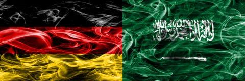 Deutschland gegen die Saudi-Arabien Rauchflaggen nebeneinander gesetzt deutsch lizenzfreie stockbilder