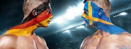 Deutschland vs Sverige Två fotboll eller fotbollsfan med flaggor vänder mot - - vänder mot på stadion Royaltyfri Bild