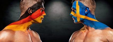 Deutschland vs Sverige Två fotboll eller fotbollsfan med flaggor vänder mot - - vänder mot på stadion Royaltyfri Fotografi
