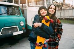 Deux à la mode et planchistes de filles de rue à la mode plaisantant et souriant Image stock
