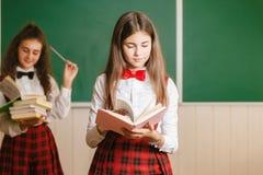 Deux écolières drôles dans l'uniforme scolaire se tiennent avec des livres sur le fond du conseil pédagogique photos stock