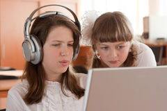 Deux écolières effectue la tâche utilisant le cahier Photographie stock libre de droits