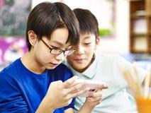 Deux écoliers élémentaires asiatiques jouant le jeu avec le téléphone portable Photographie stock libre de droits
