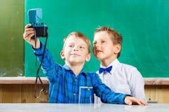 Deux écoliers font le selfie au tableau noir à l'école Photos libres de droits