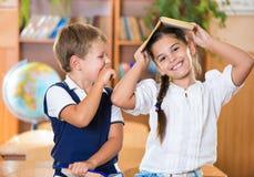 Deux écoliers heureux ont l'amusement dans la salle de classe Photo libre de droits