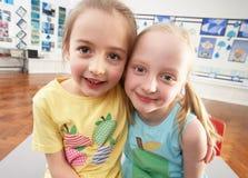 Deux écoliers primaires féminins dans la salle de classe Photo stock