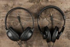 Deux écouteurs et la corde symbolique d'un amour pour la musique sur un fond en bois antique de texture Image stock